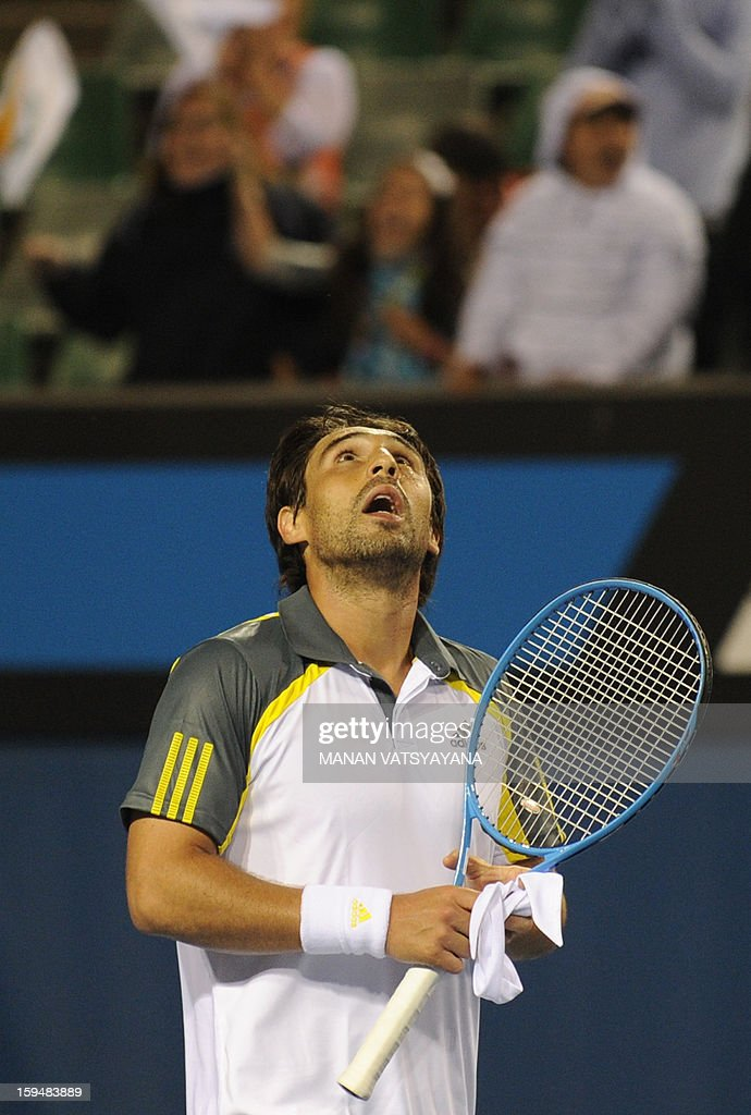 Spectators watch as Marcos Baghdatis of Cyprus celebrates after victory in his men's singles match against Albert Ramos of Spain on the first day of the Australian Open tennis tournament in Melbourne early January 15, 2013.
