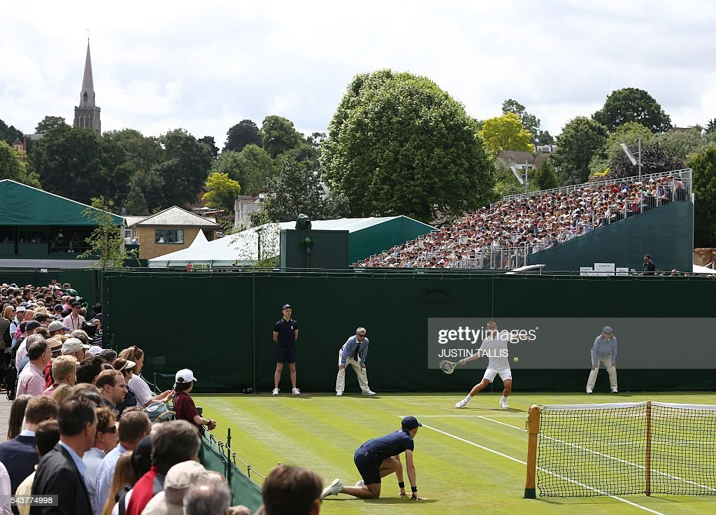 Spectators watch as Russia's Mikhail Youzhny returns on the fourth day of the 2016 Wimbledon Championships at The All England Lawn Tennis Club in Wimbledon, southwest London, on June 30, 2016. / AFP / JUSTIN