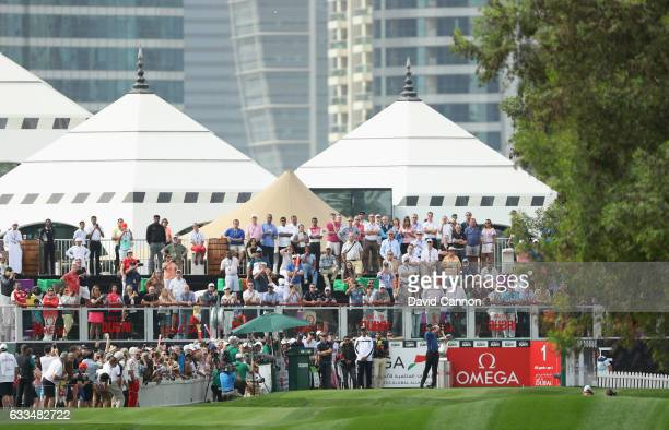 Spectators watch as Tiger Woods of the United States tees off on the 1st hole during the first round of the Omega Dubai Desert Classic at Emirates...