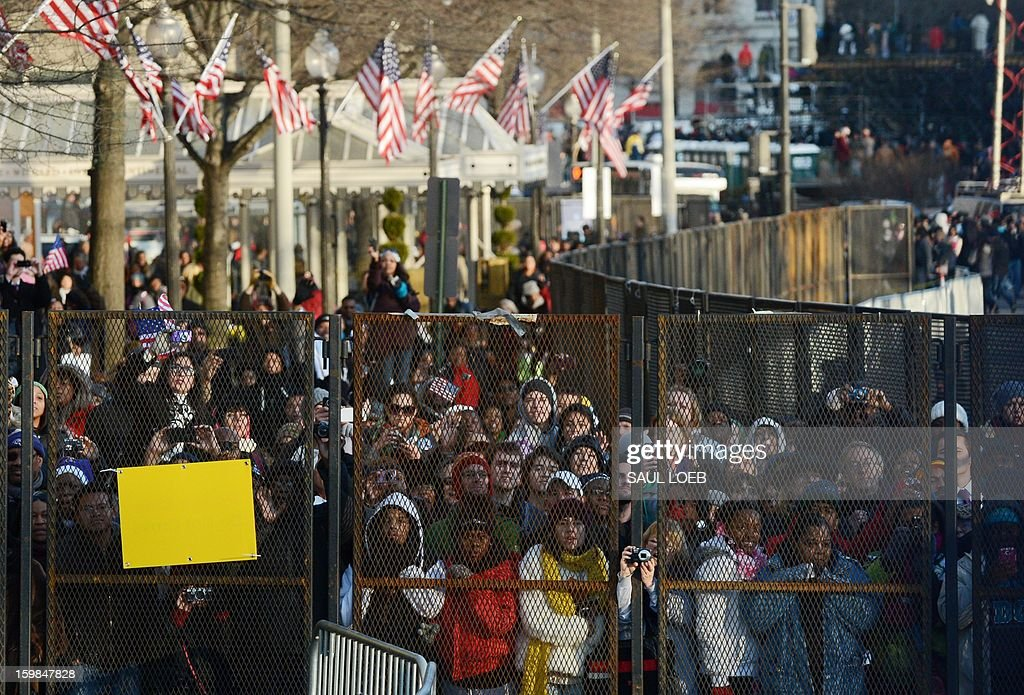 Spectators watch as US President Barack Obama and First Lady Michelle Obama's motorcade travels along Pennsylvania Avenue during the parade following Obama's second inauguration as the 44th US president on January 21, 2013 in Washington, DC. AFP PHOTO / Saul LOEB