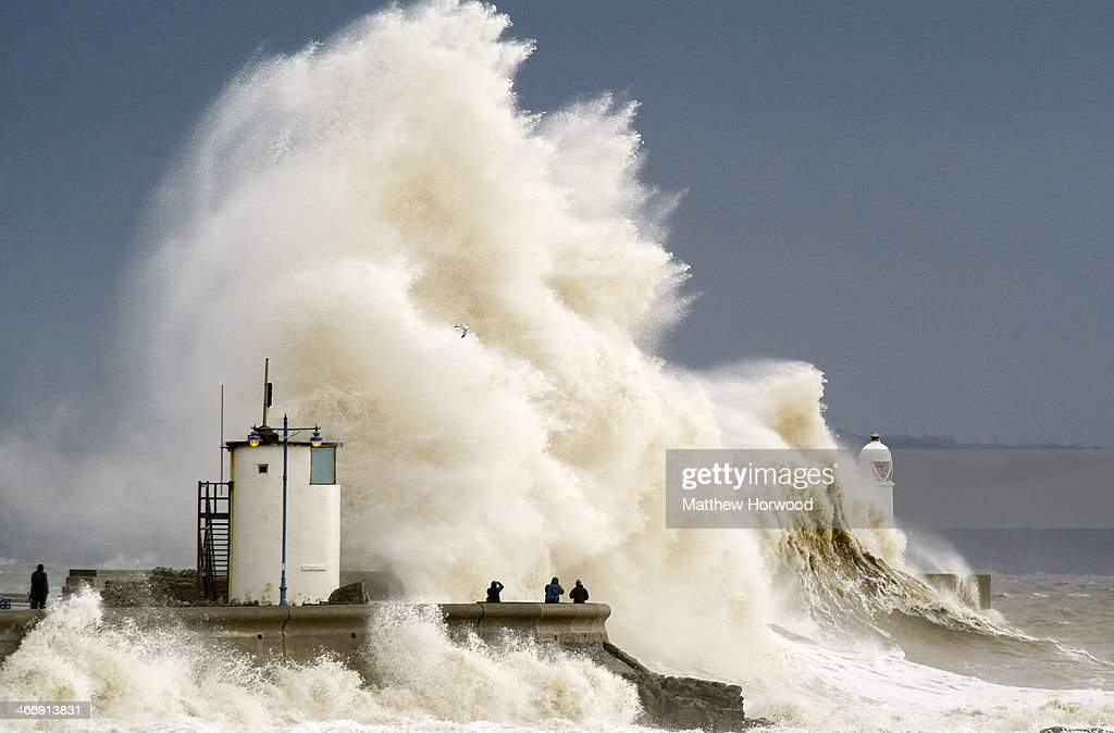 Spectators watch as waves break over the harbour wall at Porthcawl during a high tide on February 5, 2014 in Porthcawl, United Kingdom. High tides combined with gale force winds and further heavy rain mean some parts of the UK are bracing themselves for more flooding.