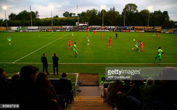 Spectators watch from the stands during the EFL Cup football match between Forest Green Rovers and MK Dons at The New Lawn stadium in Nailsworth...