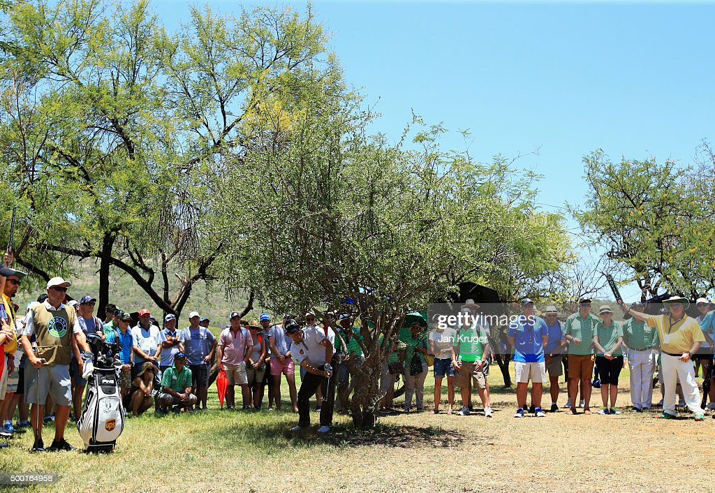 Spectators watch Louis Oosthuizen of South Africa play his second shot on the 1st hole from behind a tree during the final round on day four of the Nedbank Golf Challenge at Gary Player CC on December 6, 2015 in Sun City, South Africa.