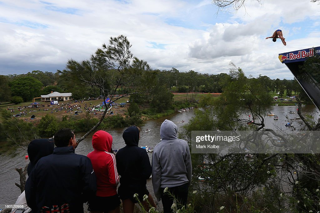 Spectators watch on as a competitor dives during the Red Bull Cliff Diving qualifying round in the Hawkesbury River on February 2, 2013 in Sydney, Australia.