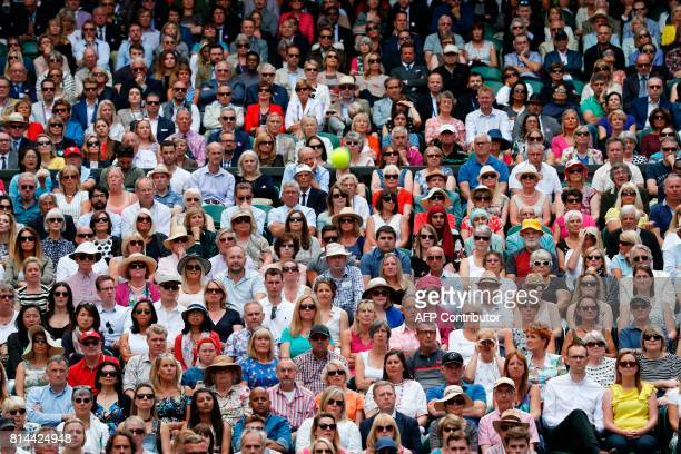 Spectators watch the ball as Croatia's Marin Cilic plays against US player Sam Querrey during their men's singles semifinal match on the eleventh day...