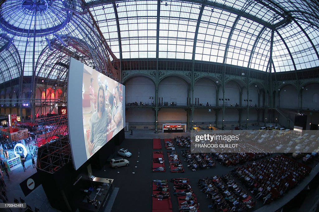 Spectators watch The Big Lebowski at the Grand Palais in Paris, on June 11, 2013, during the Cinema Paradiso, the transformation of the Grand Palais into a giant indoor drive-in replica by French cinema company MK2, that takes place from June 10 to June 21.