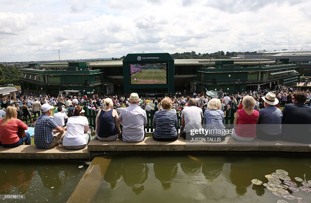 Spectators watch the big screen from Murray mount on the fourth day of the 2016 Wimbledon Championships at The All England Lawn Tennis Club in Wimbledon, southwest London, on June 30, 2016. / AFP / JUSTIN