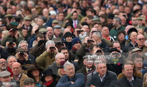 Spectators watch the first race during Ladies Day at the Cheltenham Festival at Cheltenham Racecourse on March 11 2015 in Cheltenham England