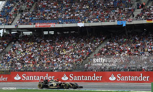 Spectators watch the German Formula One Grand Prix at the Hockenheimring racing circuit in Hockenheim southern Germany on July 20 2014 MercedesAMG's...