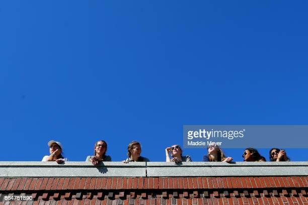 Spectators watch the Head of the Charles Regatta from the Eliot Bridge on October 21 2017 in Boston Massachusetts