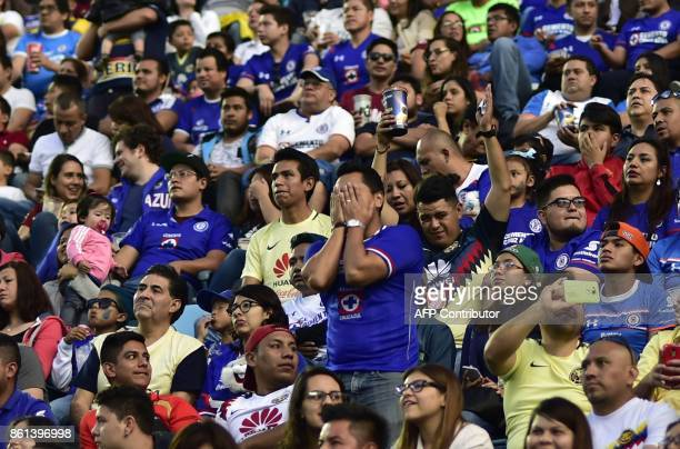Spectators watch the Mexican Apertura football tournament match between Cruz Azul and America from the stands of the Azul stadium in Mexico City on...