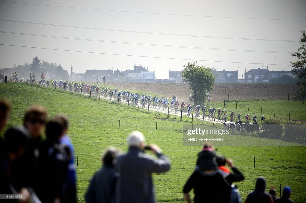 Spectators watch the pack riding through the countryside during the 112th edition of the Paris-Roubaix one-day classic cycling race on April 13, 2014 between Compiegne and Roubaix, northern France. Netherland's Niki Terpstra (Omega Pharma-Quick Step) won the race.