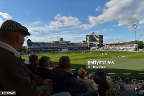 Spectators watch the play in the evening light on the first day of the second Test Match between England and South Africa at Trent Bridge cricket...