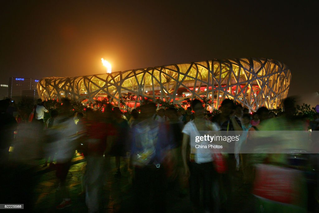 Spectators watch the shining Olympic flame outside the National Stadium during the Opening Ceremony for the Beijing 2008 Olympic Games on August 8, 2008 in Beijing, China.