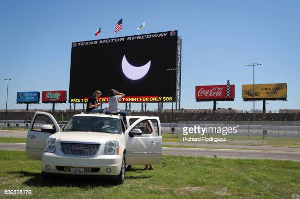 Spectators watch the solar eclipse as it is broadcast on Big Hoss at Texas Motor Speedway on August 21 2017 in Fort Worth Texas Millions of people...