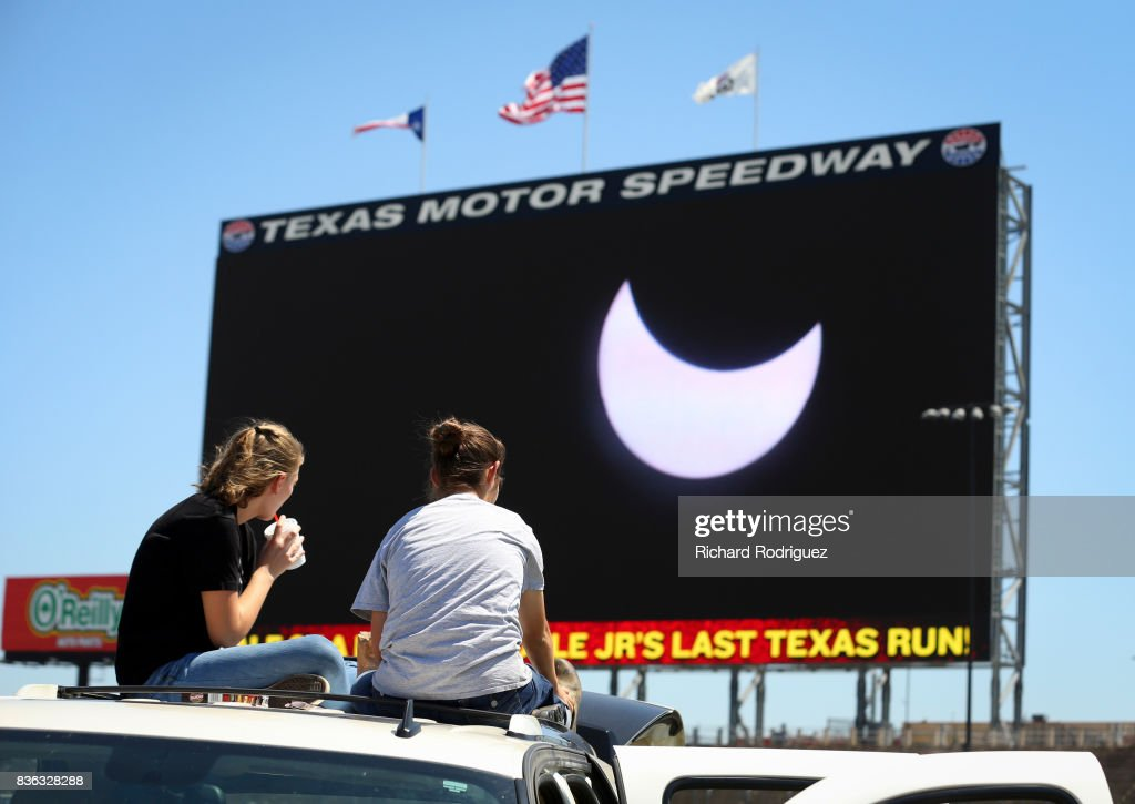 Spectators watch the solar eclipse as it is broadcast on Big Hoss at Texas Motor Speedway on August 21, 2017 in Fort Worth, Texas. Millions of people have flocked to areas of the U.S. that are in the 'path of totality' in order to experience a total solar eclipse. During the event, the moon will pass in between the sun and the Earth, appearing to block the sun. Fort Worth residents will see about 75 percent of the sun blocked by the moon.