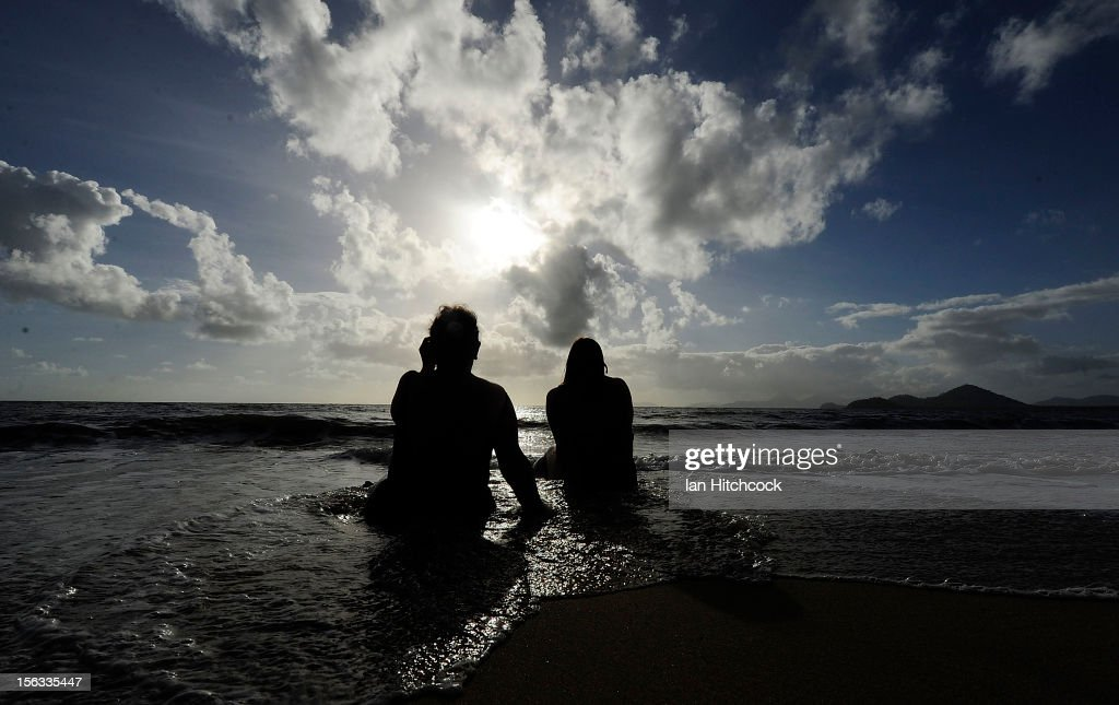 Spectators watch the solar eclipse while sitting in the surf on November 14, 2012 in Palm Cove, Australia. Thousands of eclipse-watchers have gathered in part of North Queensland to enjoy the solar eclipse, the first in Australia in a decade.