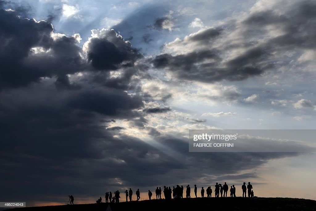 Spectators watch the solar-powered Solar Impulse 2 aircraft landing after its first flight on June 2, 2014 in Payerne, Switzerland, under a cloud covered sky. The aircraft, which was unveiled on April 9, weighs 2.4 tons with a wingspan of 72 meters and more than 17,000 solar cells. The attempt to fly around the world in stages using only solar energy will be made in 2015. AFP PHOTO / POOL / FABRICE COFFRINI