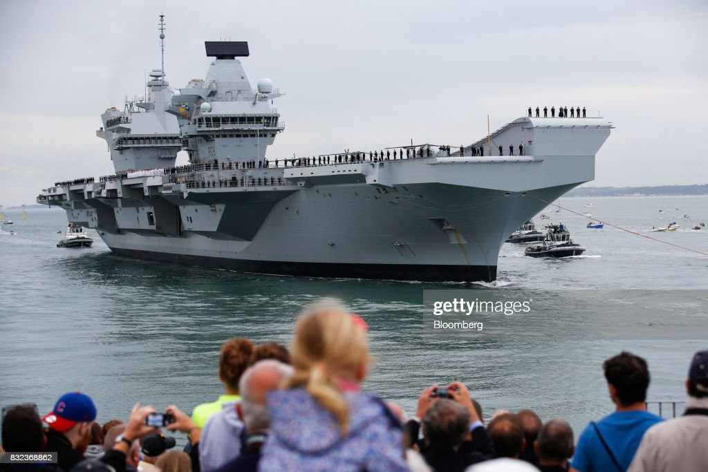 Spectators watch the U.K.'s Royal Navy new aircraft carrier, HMS Queen Elizabeth arrives at its home port in Portsmouth, U.K., on Wednesday, Aug. 16, 2017. The largely French-designed ship will carry 40 aircraft and about 700 crew members was built by a joint venture between BAE Systems Plc, Babcock International Group Plc and Thales SA. Photographer: Luke MacGregor/Bloomberg via Getty Images