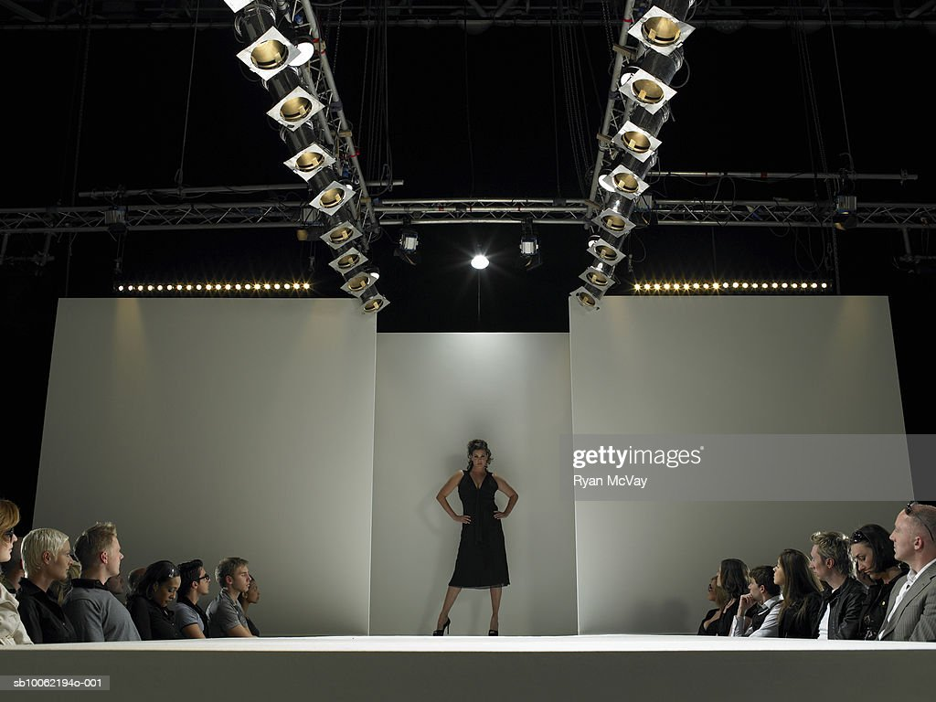 Spectators watching fashion model on catwalk : Stock Photo