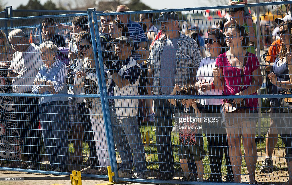 Spectators watching the Toronto Marathon near the finish line are corralled behind a fence.