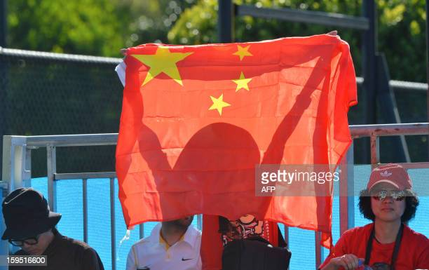 Spectators wave a flag as they cheer for Wu Di of China during his men's singles match against Ivan Dodig of Croatia on the second day of the...