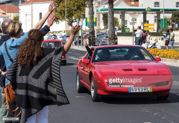 Spectators wave and are being waved back by Cascais Classic Motor Show participants driving a car through Avenida Marginal on September 17 2017 in...