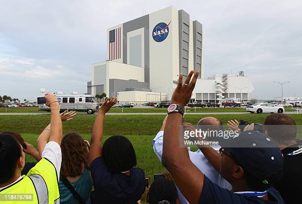 Spectators wave as the 'Astrovan' carrying the space shuttle astronauts makes its way to the launchpad at the Kennedy Space Center July 8 2011 in...