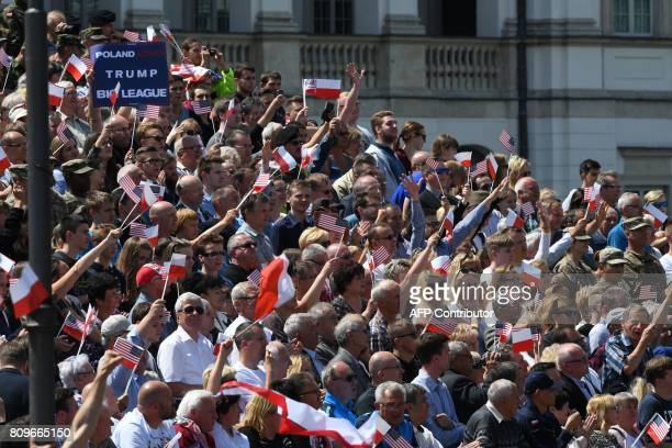 Spectators wave as US President Donald Trump gives a speech in front of the Warsaw Uprising Monument on Krasinski Square during the Three Seas...