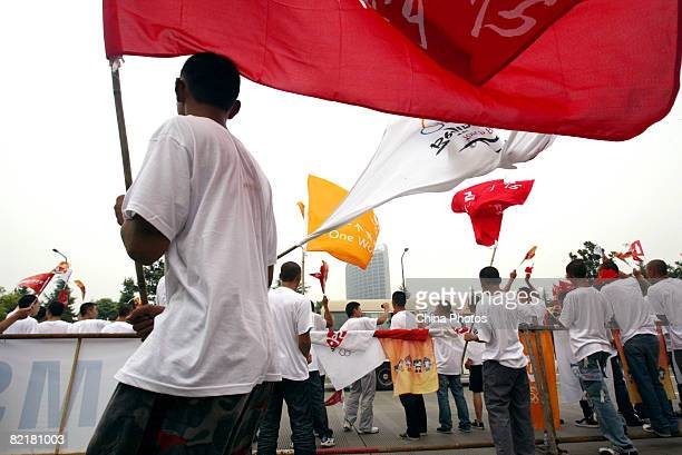 Spectators wave flags during the Chengdu leg of Beijing Olympic torch relay on August 5 2008 in Chengdu of Sichuan Province China The threeday...