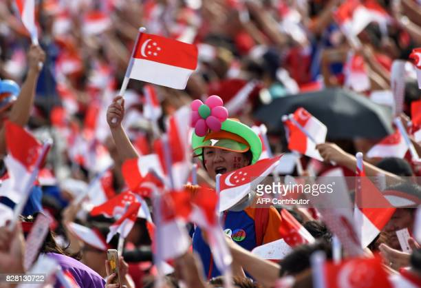Spectators wave Singaporean national flags during their country's 52nd National Day parade and celebration in Singapore on August 9 2017 / AFP PHOTO...