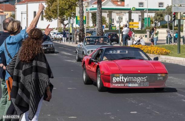Spectators wave to a Cascais Classic Motor Show participant driving a Ferrari through Avenida Marginal on September 17 2017 in Estoril Portugal More...