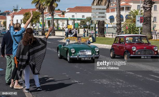 Spectators wave to Cascais Classic Motor Show participants driving classic MG and Mini through Avenida Marginal on September 17 2017 in Estoril...