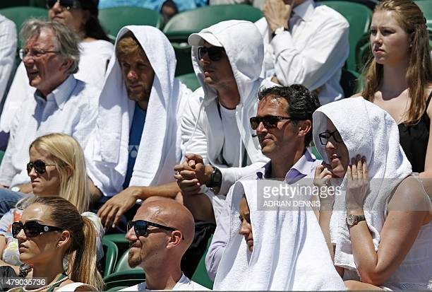 Spectators wear towels on their heads to shade them from the Sun on day two of the 2015 Wimbledon Championships at The All England Tennis Club in...