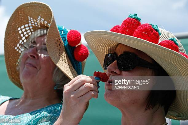 Spectators wearing strawberrythemed hats eat strawberries during a match on day six of the 2015 Wimbledon Championships at The All England Tennis...