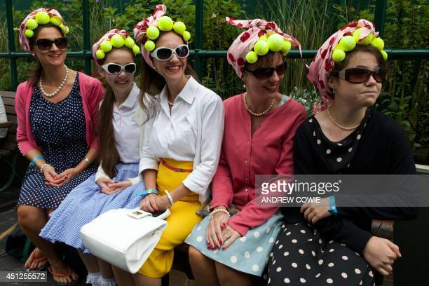 Spectators wearing tennis ball accessories pose on day four of the 2014 Wimbledon Championships at The All England Tennis Club in Wimbledon southwest...
