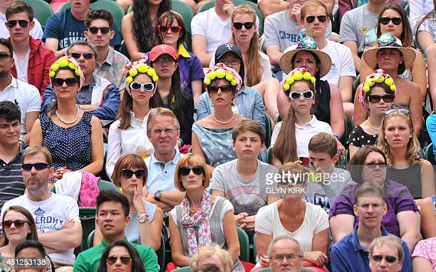 Spectators weat tennis ball hat accessories as they watch Czech Republic's Lukas Rosol play against Spain's Rafael Nadal during their men's singles...