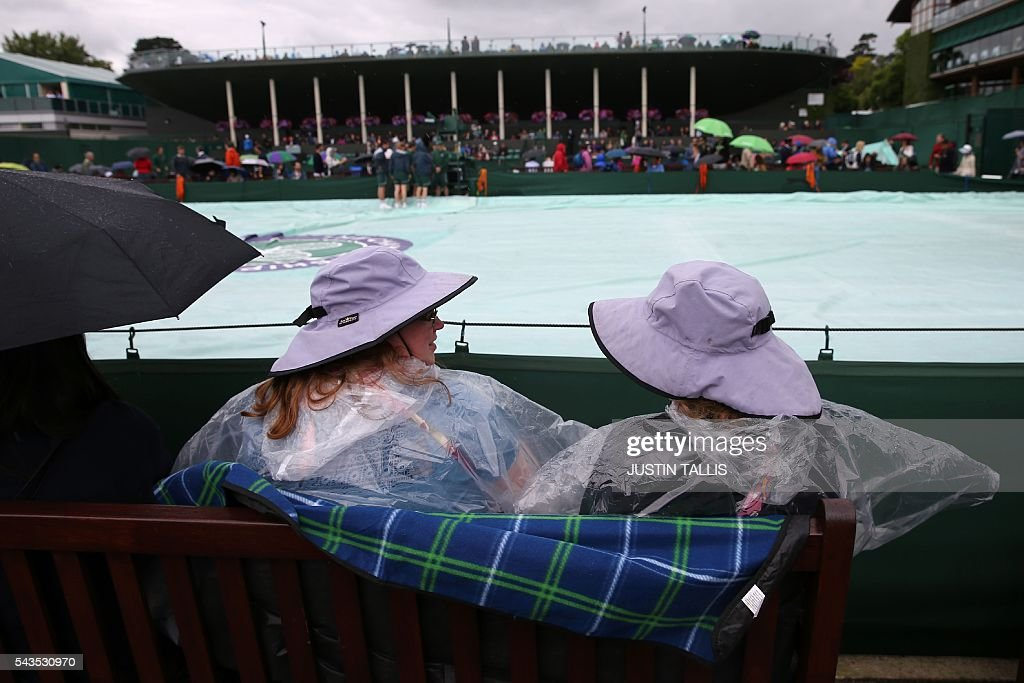 Spectators with umbrellas and rain gear sit alongside outer courts with the rain covers deflated but still on on the rain delayed third day of the 2016 Wimbledon Championships at The All England Lawn Tennis Club in Wimbledon, southwest London, on June 29, 2016. / AFP / JUSTIN