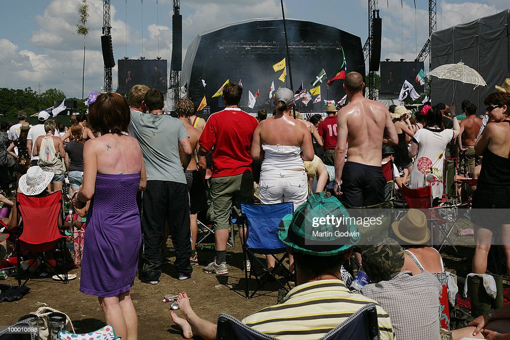 Spectators with wide waists at The Other Stage at Glastonbury, under the hot sun, with burnt shoulders and oily suncream, 27th June 2009.