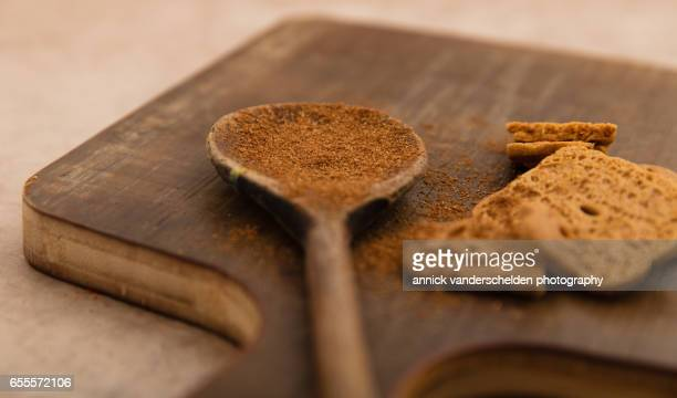 Speculoos cookies and powdered speculoos on wooden spoon.
