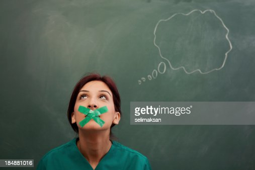 Speech bubble on blackboard, woman's moth closed with adhesive tape
