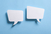 Photo of paper speech bubbles on blue background.
