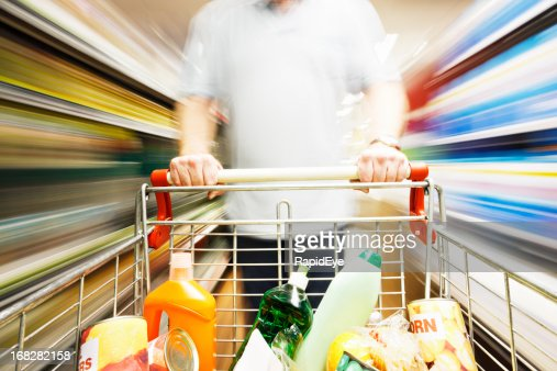 Speed blurs male shopper in supermarket with full shopping cart
