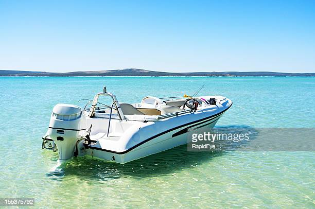 Speed boat moored in the shallows of turquoise lagoon