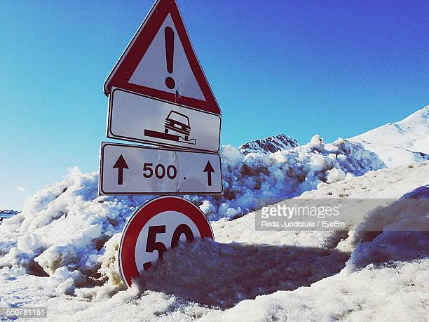 Speed Limit Sign On Snowcapped Mountain Against Clear Blue Sky