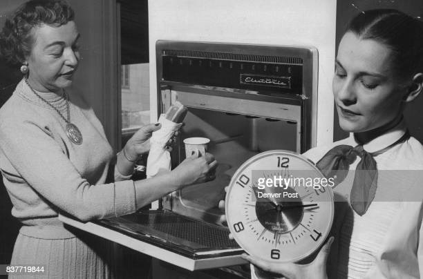 Speed of electronic cooking is demonstrated by Mrs Ruth Laird Denver home economist who places a mustard coated hot dog wrapped with paper napkin and...