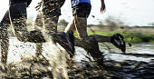 Three young adults are testing their agility and endurance during an extreme challenge of running through mud outdoors.