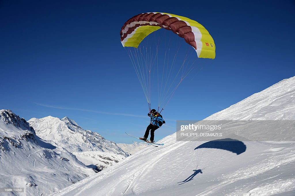 A speed rider flies over a snowy slope on December 29, 2012, in the French Alps resort of Val d'Isere. The speed riding is an open-air sport associating the ski, the paragliding and the parachuting, and which consists in going down the snowy slopes equipped with a pair of skis and with a sail of low surface, by alternating the glide and the flight.