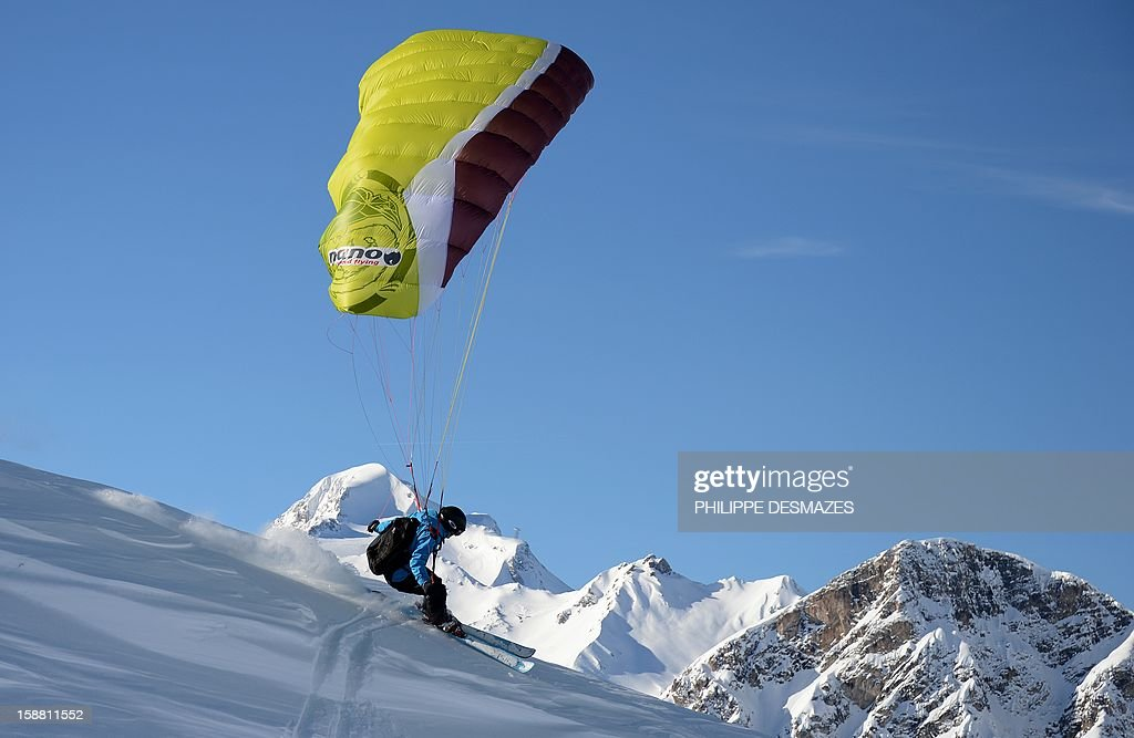 A speed rider glides on a slope on December 29, 2012, in the French Alps resort of Val d'Isere. The speed riding is an open-air sport associating the ski, the paragliding and the parachuting, and which consists in going down the snowy slopes equipped with a pair of skis and with a sail of low surface, by alternating the glide and the flight.