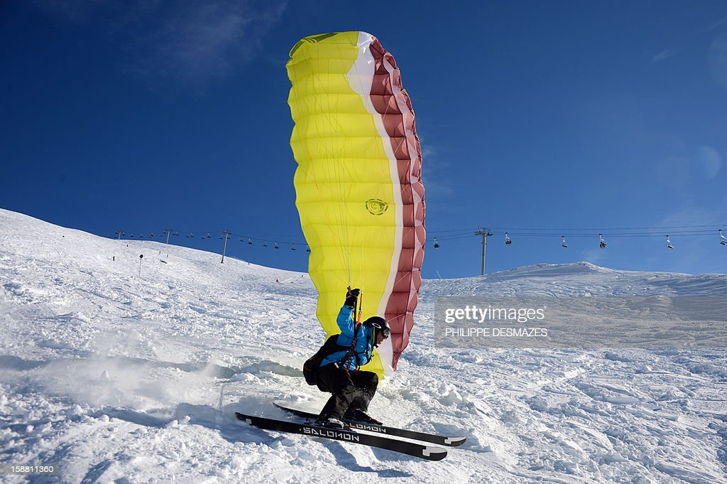 A speed rider glides on a snowy slope on December 29, 2012, in the French Alps resort of Val d'Isere. The speed riding is an open-air sport associating the ski, the paragliding and the parachuting, and which consists in going down the snowy slopes equipped with a pair of skis and with a sail of low surface, by alternating the glide and the flight.